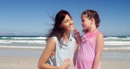 den matek : Affectionate daughter kissing her mother at beach on a sunny day