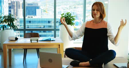 размышлять : Female executive meditating at her desk in office