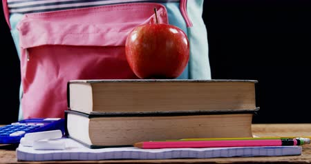 öğrenme : Apple on book stack with schoolbag against black background Stok Video
