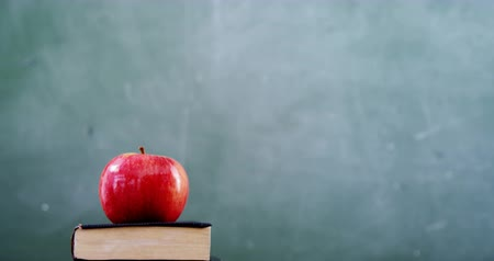 borracha : Apple on book stack with school supplies on table against chalkboard