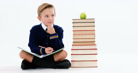 стек : Thoughtful schoolboy doing her homework against white background