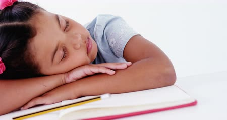 sleep : Tired schoolgirl sleeping on the book against white background