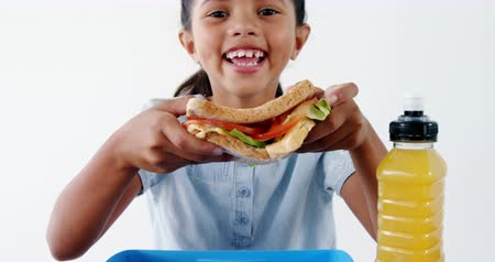 banany : Portrait of smiling cute girl holding sandwich against white background