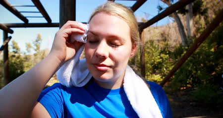 suor : Tired woman wiping sweat after workout during obstacle course in boot camp