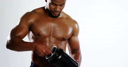 black dirt : Smiling muscular holding a protein bottle against white background