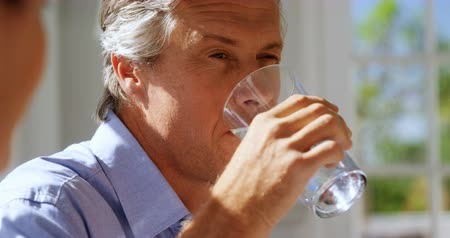 szemüveg : Close-up of man drinking water in restaurant Stock mozgókép