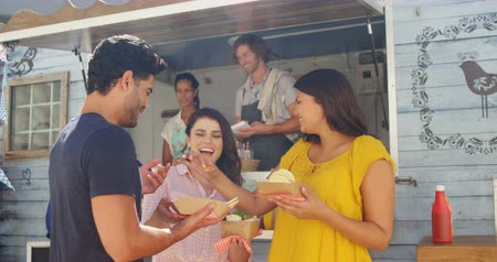 определение : Smiling friends eating snacks in food truck van
