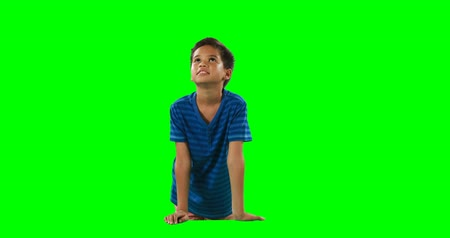 érintőképernyő : Smiling boy touching digital screen against green background 4k