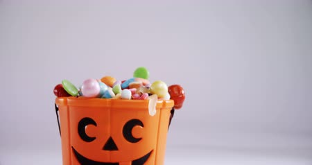 full bucket : Halloween bucket filled up with various confectioneries against white background 4k