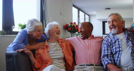 senior lifestyle : Happy senior friends having fun while relaxing on sofa at retirement home 4k