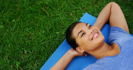 ультра : Smiling beautiful woman lying on exercise mat in garden 4k Стоковые видеозаписи