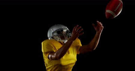 yakalamak : American football player catching the ball and running against a black background 4k