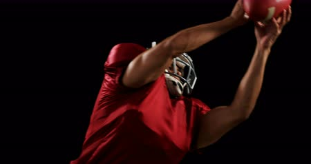 yakalamak : American football player catching the ball against a black background 4k