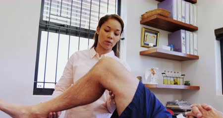терапия : Physiotherapist examining patients knee in clinic 4k
