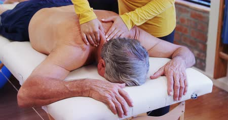 akupresura : Physiotherapist giving shoulder massage to a senior man in clinic 4k