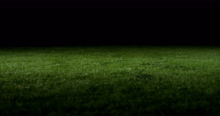 снасти : Soccer player performing a sliding tackle on playing field at night 4k