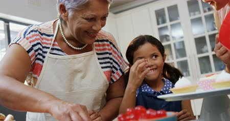 бабушка : Smiling girl eating a cherry while making cupcakes with mother and granny 4k