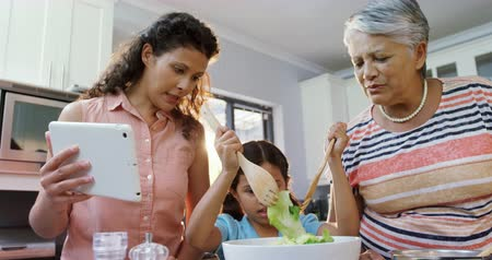 autêntico : Mother and granny assisting little girl to mix the salad at home 4K 4k