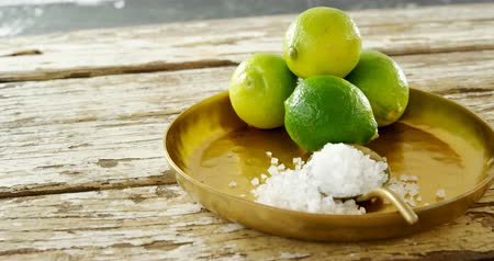 calcário : Salt and lime in a plate on wooden table 4k Stock Footage