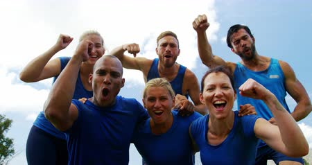 izgatott : Group of fit people cheering together in boot camp on a sunny day 4k