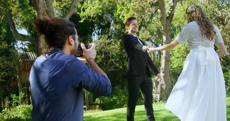weddings : Photographer taking photo of groom and bride in garden area 4K 4k