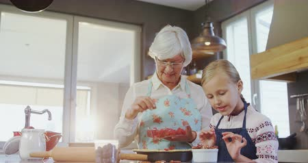 plating food : Grandmother and granddaughter plating the pie  with strawberries in the kitchen  4k