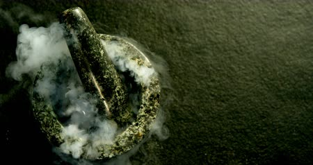 kamień : Close-up of smoke coming out of pestle and mortar on black surface 4k