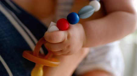 soymak : Close-up of cute little baby carrying pacifier and mother holding him at home 4k Stok Video