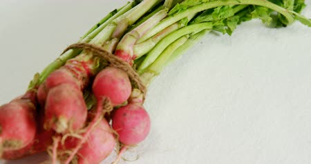 gömbölyű : Close-up of bunch of radish placed against white background 4K 4k