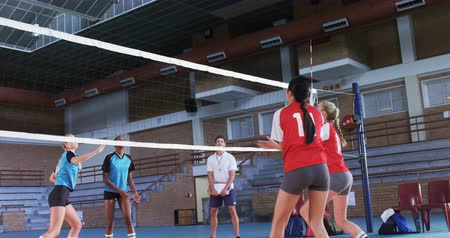koç : Female volleyball players playing volleyball in the court 4k Stok Video