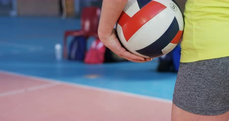 röplabda : Mid section of female player holding volleyball in the court 4k