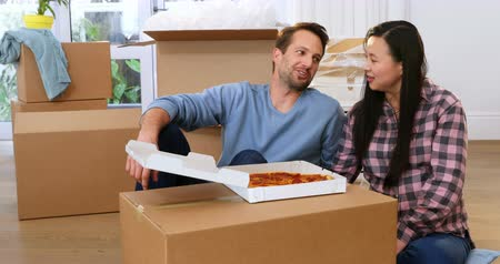 feed on : Smiling couple having pizza in new house 4k Stock Footage