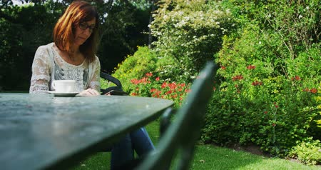 livro : Mature woman reading a book in the garden on a sunny day 4k Vídeos