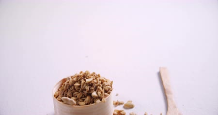 oat flakes : Oat flakes in a wooden bowl and spoon on white background 4k Stock Footage