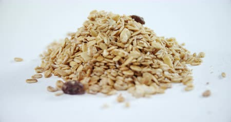 yulaf ezmesi : Close-up of crunchy granola scattered on white background 4k Stok Video