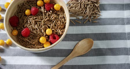 egres : Bowl of cereal bran stick with golden berries and raspberries on a tablecloth 4k
