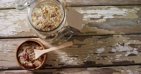 fehérjék : Bowl of breakfast cereals with jar on a wooden table 4k