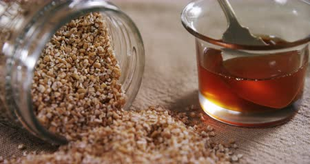 sweetener : Close-up of grains spilling out of jar with bowl of honey 4k