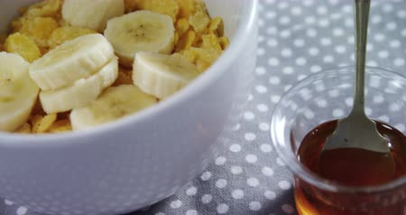 sweetener : Bowl of corn flakes with banana on a tablecloth 4k