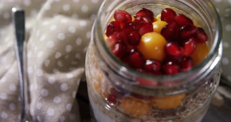 agrest : Close-up of yogurt with pomegranates and golden berries in glass jar 4k