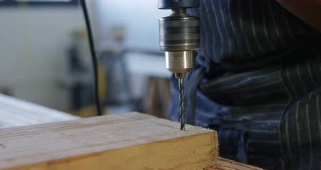 fartuch : Close-up of carpenter drilling wooden plank with machine in workshop 4k