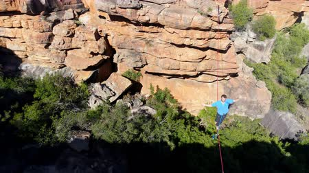 slacklining : Male highliner walkng on a rope over rocky mountains at countryside 4k