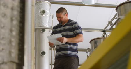 distillation tank : Male worker writing on a clipboard at factory 4k