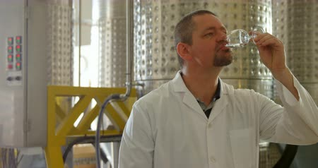 distillation : Mature male worker examining liquor in factory 4k