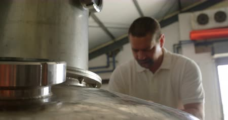 distillation : Male worker examining a distillation tank in factory 4k