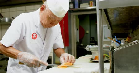 indulgência : Male chef cutting sushi in kitchen at restaurant 4k Stock Footage