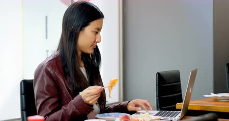 indulgência : Young woman having sushi while using laptop in restaurant 4k