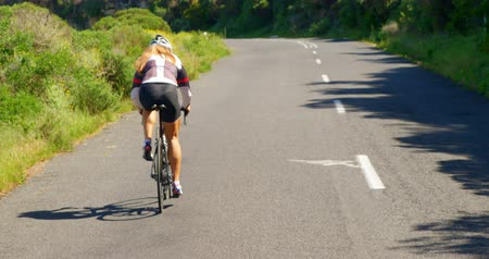 мостовая : Rear view of female cyclist cycling bicycle on a countryside road 4k