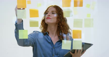 клейкий : Businesswoman writing on the sticky notes and reading them in the office 4k
