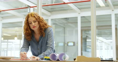 female measurements : Female architect working on blueprint in office 4k Stock Footage